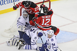 Nov 2; Newark, NJ, USA; New Jersey Devils center Ryan Carter (20) and New Jersey Devils right wing Nick Palmieri (12) crash into Toronto Maple Leafs goalie Jonas Gustavsson (50) after he made a save during the first period at the Prudential Center.
