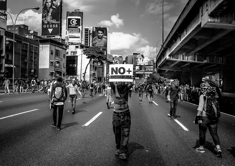 Caracas, Venezuela - 6/4/17: A protester holds a poster that read &quot;no more dictatorship&quot;  Thousands of people take Francisco Fajardo highway, the main highway in the city, in protest at the decision of the Supreme Court of Justice that orders the cessation of functions of the National Assembly. Venezuelan opposition won qualified majority of the parliament in elections one year before, liders in the region calified thise action like a coup. The year 2017 did not start with good news for Venezuelans. It had been a year since a new National Assembly elected in which opposition won an absolute majority, but the economic crisis worsened and the most optimistic forecasts estimated an inflation of 720% (It was 2700%) and shortage of food and medicines by 85%. <br />