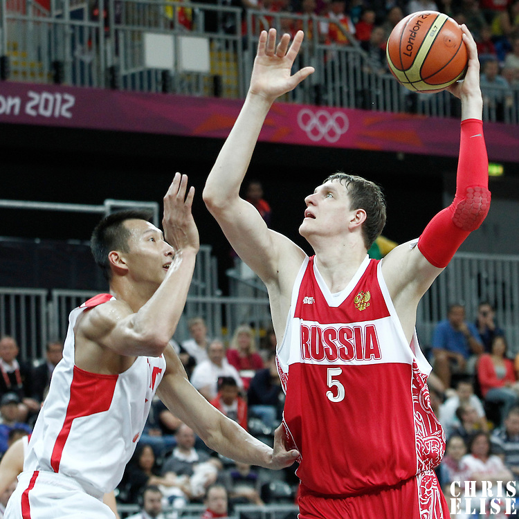 31 July 2012: Russia Timofey Mozgov goes for the skyhook over China Jianlian Yi during the 73-54 Russia victory over China, during the men's basketball preliminary, at the Basketball Arena, in London, Great Britain.