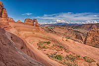 The famous Delicate Arch stands 65 feet (20 meters) above its sandstone base in the surrounding canyons and ravines in Arches National Park in eastern Utah's Moab Desert.