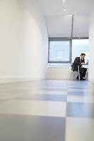 Businessman sitting Using Laptop in empty room ground view