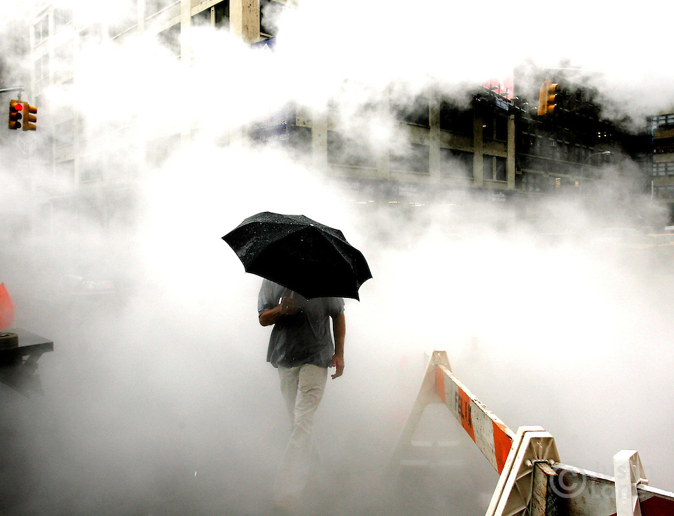epa01096131 A man with an umbrella walks through steam rising from a construction site during a rain storm in New York, USA 21 August 2007.  EPA/JUSTIN LANE