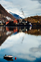 A boat floats in the Sørfjorden, near the town of Odda, Norway. The Boliden Odda Zinc smelting plant is seen in the background.