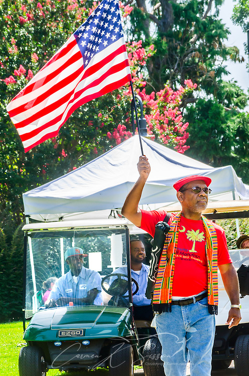 An African-American man carries an American flag outside the South Carolina State House, July 10, 2015, in Columbia, S.C. Thousands flocked to the South Carolina Statehouse to see the removal of the Confederate flag. The flag flew above the capitol dome from 1961-2000, then was moved to the grounds. The flag, which is now permanently removed, will be stored at the Confederate Relic Room and Military Museum. The House voted for its removal after the shooting of nine African-Americans at Emanuel African Methodist Episcopal Church in Charleston, June 17, 2015. Alleged shooter Dylann Roof, who published a manifesto on his website supporting white supremacist beliefs, was seen in numerous photographs holding the Confederate flag. (Photo by Carmen K. Sisson/Cloudybright)