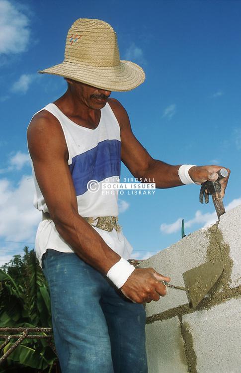 Builder cementing breeze blocks while constructing wall at Gibara; Cuba,