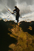 Amerindian Fisherman using bow and arrow.<br /> Grass Pond<br /> Rewa Forest<br /> GUYANA<br /> South America