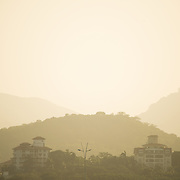The haze catches the setting sun in the hills around Panama City, Panama.