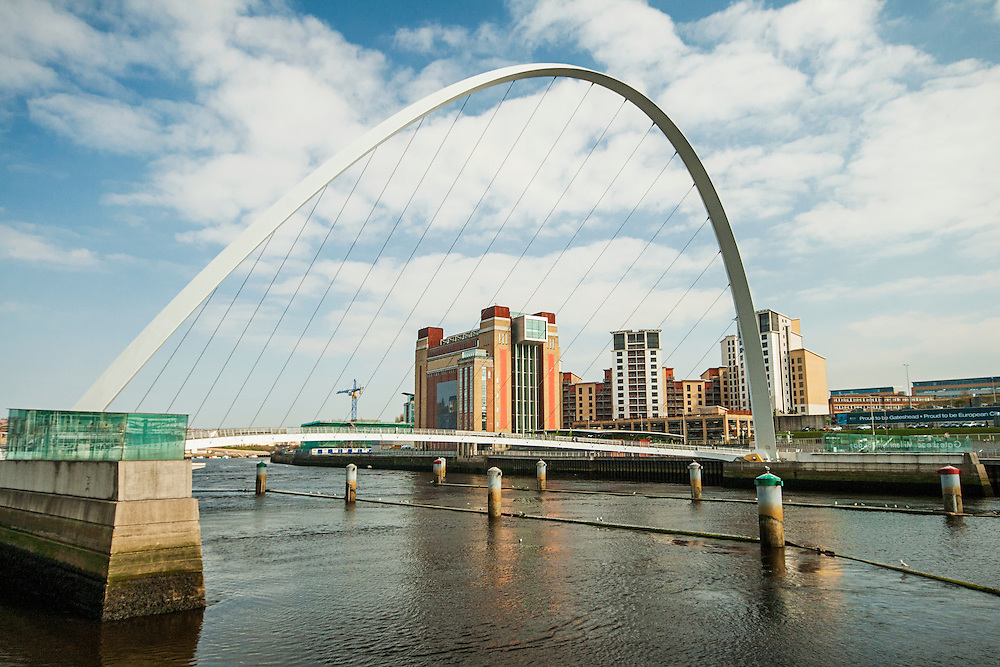 The Millenium Bridge is a pedestrian footbridge spanning the River Tyne between Newcastle and Gateshead in the North East of England.It was opened to the public on 17 September 2001,]and was dedicated by Queen Elizabeth II on 7 May 2002. In the background stands the Baltic Arts Centre.