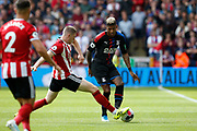John Lundstram of challenges Patrick van Aanholt of Crystal Palace during the Premier League match between Sheffield United and Crystal Palace at Bramall Lane, Sheffield, England on 18 August 2019.