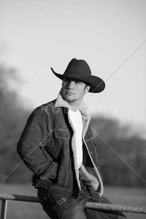 sexy cowboy at sunset in a sheepskin and suede jacket outdoors sitting on a fence