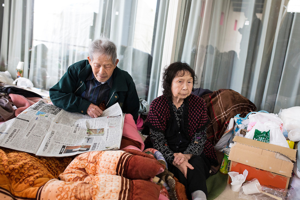 KUMAMOTO, JAPAN - APRIL 20: A family, survived from earthquake, reads newspaper in the morning on April 20, 2016 in Mashiki Gymnasium evacuation center, Kumamoto, Japan. As of April 45 people were confirmed dead after strong earthquakes rocked Kyushu Island of Japan. Nearly 11,000 people are reportedly evacuated after the tremors Thursday night at magnitude 6.5 and early Saturday morning at 7.3.<br />