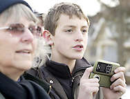 """A young man waits with a camera phone for Hillary Clinton to come out of the Fair River Oaks Council after attending a """"Roundtable Discussion On Home Foreclosure Crisis,"""" Thursday, February 14, 2008."""