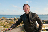 Outdoor portraits of Steven Foster, real estate agent, at the beach near Cattle Point in Victoria, BC on a sunny winter day.