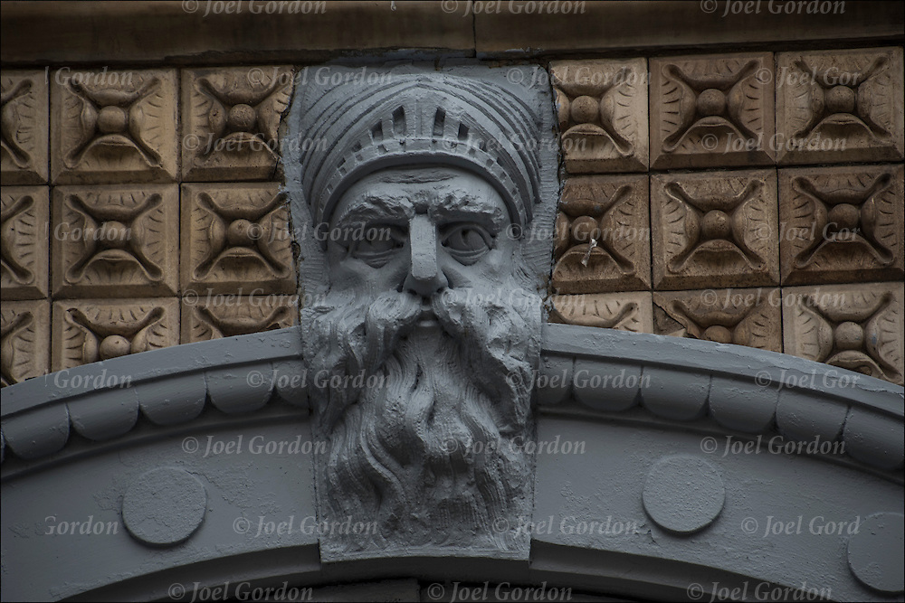 Stonework on side of 19th century building of carved face in the East Village, NYC