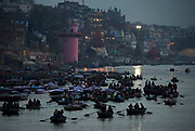 Dawn breaks over the Ganges at Varanasi as boatloads of pilgrims jostle for position.
