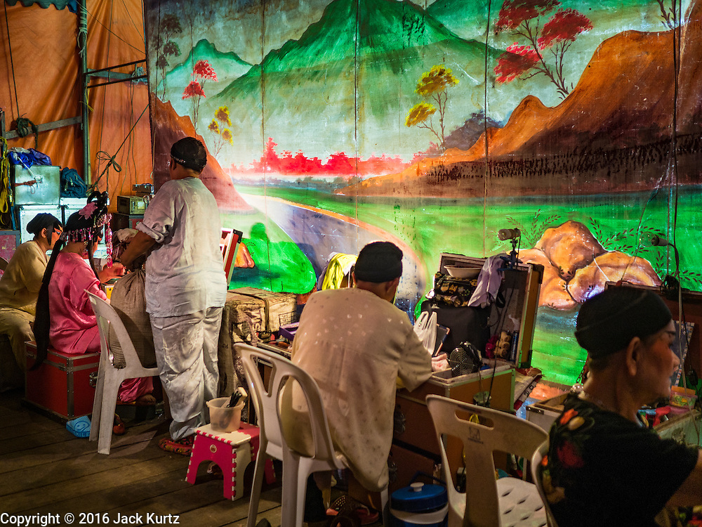 17 FEBRUARY 2016 - BANGKOK, THAILAND:  Members of the cast backstage before a Chinese opera performance in Bangkok. They're from a small troupe that travels from Chinese shrine to Chinese shrine performing for a few nights before going to another shrine. They spend about half the year touring in Thailand and the other half of the year touring in Malaysia. Members of the troupe are paid about 5,000 Thai Baht per month (about $140 US). Chinese opera was once very popular in Thailand, where it is called Ngiew. It is usually performed in the Teochew language. Millions of Chinese emigrated to Thailand (then Siam) in the 18th and 19th centuries and brought their culture with them. Recently the popularity of ngiew has faded as people turn to performances of opera on DVD or movies. There are still as many 30 Chinese opera troupes left in Bangkok and its environs. They are especially busy during Chinese New Year and Chinese holiday when they travel from Chinese temple to Chinese temple performing on stages they put up in streets near the temple, sometimes sleeping on hammocks they sling under their stage. Most of the Chinese operas from Bangkok travel to Malaysia for Ghost Month, leaving just a few to perform in Bangkok.    PHOTO BY JACK KURTZ