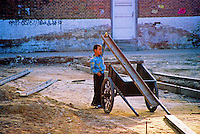 China, Datong, 2008. A boy entertains himself near an apartment construction site. Though it risks exceeding demand for office space in big cities, China's building boom has benefited ordinary citizens, creating thousands of new homes.