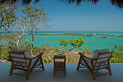 Two chairs over vivid green Caribbean water, and a cloudless blue sky, Rosario archipelago, Cartagena, Colombia, South America