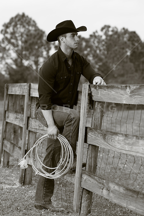 handsome cowboy leaning on a fence with a lasso his his hand