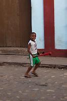Young boy playing baseball on the streets of Trinidad, Cuba.