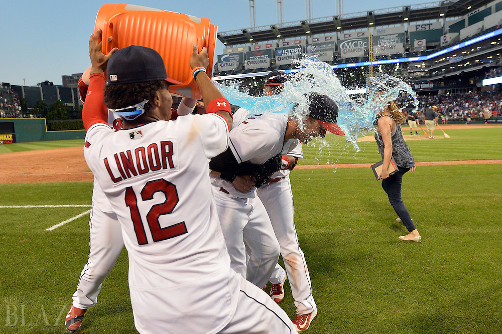 Sep 4, 2016; Cleveland, OH, USA; Cleveland Indians shortstop Francisco Lindor (12) dumps a bucket of gatorade on Cleveland Indians right fielder Lonnie Chisenhall (8) after Chisenahll hit a game winning single during the ninth inning to beat the Miami Marlins 6-5 at Progressive Field. Mandatory Credit: Ken Blaze-USA TODAY Sports