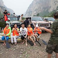 BEIJING, JUNE 24, 2013 : Li Xiaohua schreitet zum naechsten Programmpukt vor und bruellt die Miglieder seines Clubs an, sich fuer das zweite Gruppenbild auf ein Schlauchboot zu setzen. Li gruendete den Club vor einem Jahr . Mitglieder koennen nur per Einladung beitreten und muessen ein gewisses Einkommen nachweisen koennen.