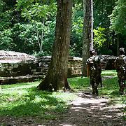 Soldiers walk near an ancient Mayan ball court in Copan Ruins, Honduras. June 2009.  (Photo/William Byrne Drumm)