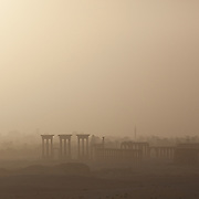 Silhouette of Palmyra columns and tetrapylon, early morning, just after a desert sandstorm. The modern city of Tadmur with its mosques can be seen in the distance.