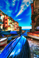 """""""Boats patiently waiting to set sail in Riomaggiore""""…<br /> <br /> I began my daily journey at the northern most town of Monterosso and took the train to the southernmost town of Riomaggiore. Upon arriving in this picturesque seaside village and moving down to the water's edge, I noticed proprietor Francesco in front of a tiny boat rental sign.  After arranging an evening sail up the coast, I was able to focus on the colorful persona of Riomaggiore. That evening I sailed up the coast photographing each Cinque Terre town along the way aboard the Angelina Dada. Upon arriving back home in Monterosso, soft light illuminated the sky and azure sea of the Mediterranean convincing me to sail all the way back to Riomaggiore with my gracious guides Claudio and Eddie of """"Cinque Terre dal Mare"""" sailing excursions. We arrived just in time for a perfect sunset. After a nice dinner...I caught the last train at midnight back home to Monterosso. A very long day, but worth every minute!"""