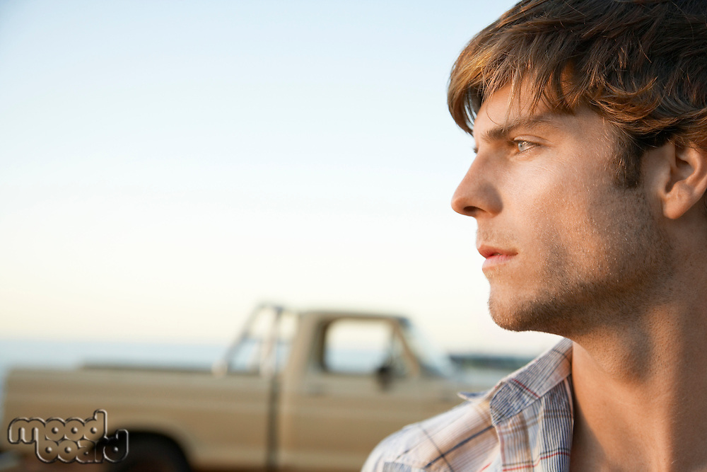 Young man head and shoulders profile in front of van