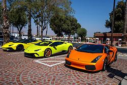 Three Lamborgini sports cars parked in front of a Tesla Super Charger station, Harris Ranch (3O8), Coalinga, California, United States of America