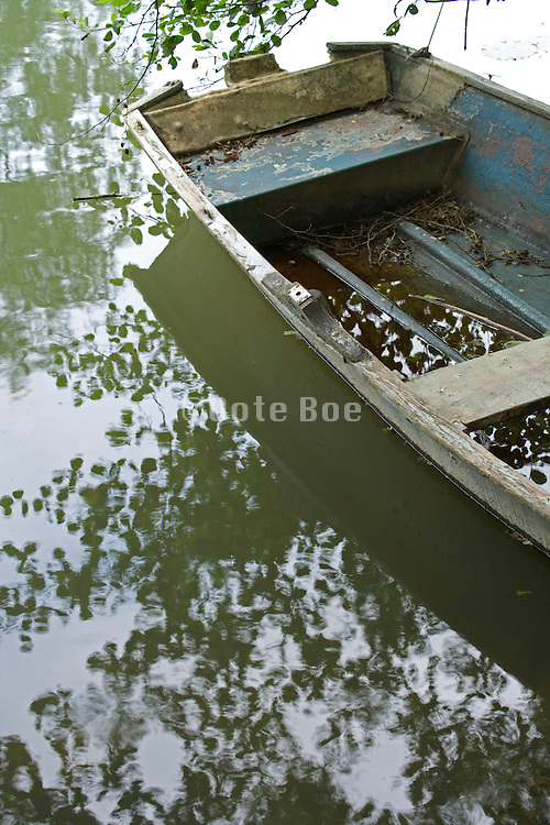 moored wooden row boat with some water in its hull