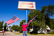 "03 AUGUST 2020 - JEWELL, IOWA: GARREN ZANKER, manager of the Jewell Market, adjusts the American flags on the sign in front of the store. The only grocery store in Jewell, a small community in central Iowa, closed in 2019. It served four communities within a 20 mile radius of Jewell. Some of the town's residents created a cooperative to reopen the store. They sold shares to the co-op and  held fundraisers through the spring. Organizers raised about $225,000 and bought the store, which had its ""soft opening"" July 8. The store celebrated its official reopening Monday August 3. Before the reopening, Jewell had been a ""food desert"" for seven months. The USDA defines rural food deserts as having at least 500 people in a census tract living 10 miles from a large grocery store or supermarket. There is a convenience store in Jewell, but it sells mostly heavily processed, unhealthy snack foods that are high in fat, sugar, and salt.   PHOTO BY JACK KURTZ"