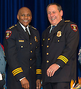 Retiring Houston ISD Chief of Police Jimmy Dotson, left, and Chief Robert Mock, right, share a laugh after Mock was sworn into office, January 6, 2014, at the High School for Law Enforcement and Criminal Justice.