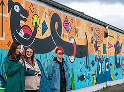 Pictured: Edinburgh Dog & Cat Home Mural Unveiling. , Edinburgh, Scotland, 03 May 2019. (from L to R) Alanna Brady, Special Gifts Fund Raiser at the Edinburgh Dog & Cat Home, Charlotte Johnson, Edinburgh Shoreline Project Manager and mural artist Katie Guthrie. Both dogs are looking for a good home. The 80 foot mural is unveiled today as a colourful addition to Seafield promenade. It is designed and painted by local artists Studio N_Name. It depicts the people, heritage and environment of the local community and features flora, fauna and historic elements of the local coastline. It has been made possible through through partnership with Edinburgh Shoreline Project. It is on the seafront wall of the dog & cat home which rescues, reunites and rehomes lost, stray and abandoned dogs and cats across Edinburgh and the Lothians, caring for 2,367 dogs and 771 cats in 2018.<br /> Sally Anderson | EdinburghElitemedia.co.uk