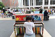A girl plays one of the 88 Sing for Hope Pianos, supported by Chobani, Inc., at the Josie Robertson Plaza at Lincoln Center, Sunday, June 16, 2013. The event celebrates the conclusion of the Sing for Hope Pianos project, a two-week public art installation around the five boroughs of New York.  (Photo by Diane Bondareff/Invision for Sing for Hope)
