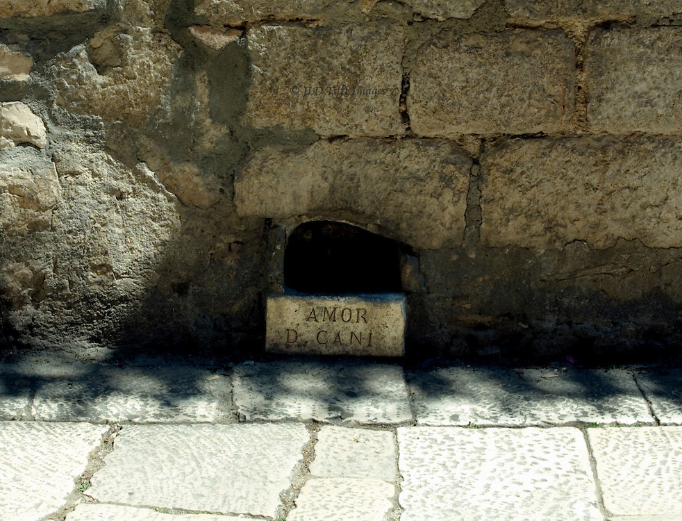 "Sibenik, water dish for dogs built into a Renaissance wall, inscribed ""AMOR D' CANI""  Streetscape with marble pavement."