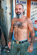 A Lebanese man stands outside a shop in the Shatila neighborhood of Beirut, numerous tattoos on his body. The man is a Shia Muslim, and his tattoos include family members and Woody Woodpecker.