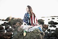 Beautiful woman draped in the american flag and tibetan prayer flags.