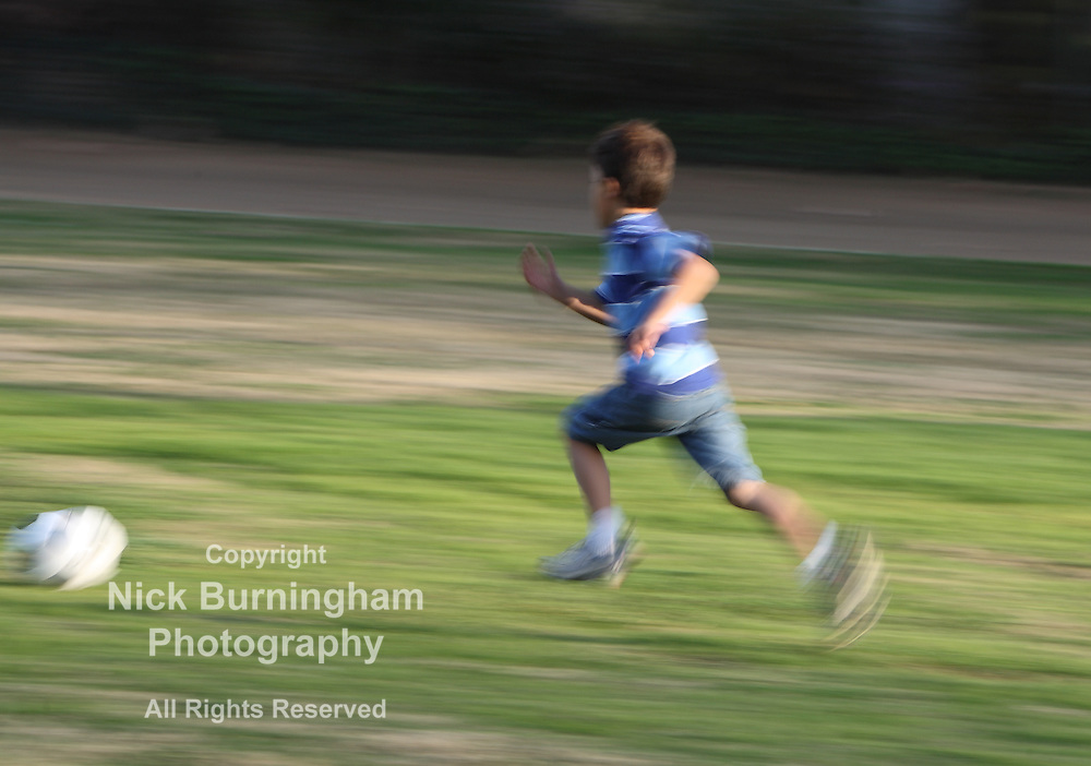 Motion blurred boy running fast after soccer ball on green grassy background
