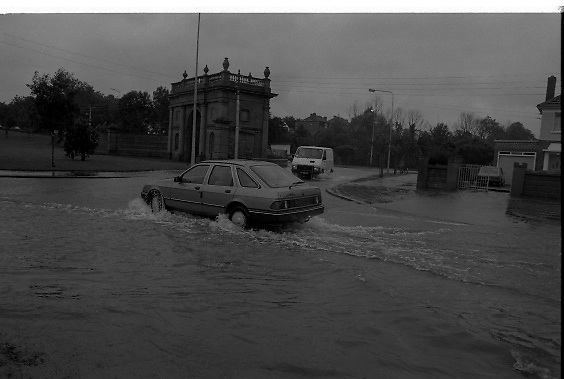 """Flooding at the Dodder..1986..26.08.1986..08.26.1986..28th August 1986..As a result of Hurricane Charly (Charlie) heavy overnight rainfall was the cause of severe flooding in the Donnybrook/Ballsbridge areas of Dublin. In a period of just 12 hours it was stated that 8 inches of rain had fallen. The Dodder,long regarded as a """"Flashy"""" river, burst its banks and caused great hardship to families in the 300 or so homes which were flooded. Council workers and the Fire Brigades did their best to try and alleviate some of the problems by removing debris and pumping out some of the homes affected..Note: """"Flashy"""" is a term given to a river which is prone to flooding as a result of heavy or sustained rainfall...Photograph of motorists trying to avoid the worst of the flooding by driving on the 'wrong' side of the road. Motorists were advised to be vigilant as manhole covers had been displaced by the water pressure and were lying unseen underwater."""