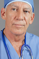 Close-up view of senior male surgeon over gray background
