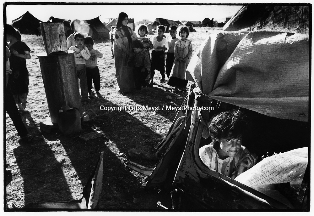 SULEYMANIYAH, KURDISTAN, IRAQ, JULY 1994. Refugees from Halabja have set up camp in old car wrecks and makeshift tents.  All over the Kurdish autonomous region fighting broke out between the KDP and PUK and smaller kurdish factions. ©Photo by Frits Meyst/NewsImages
