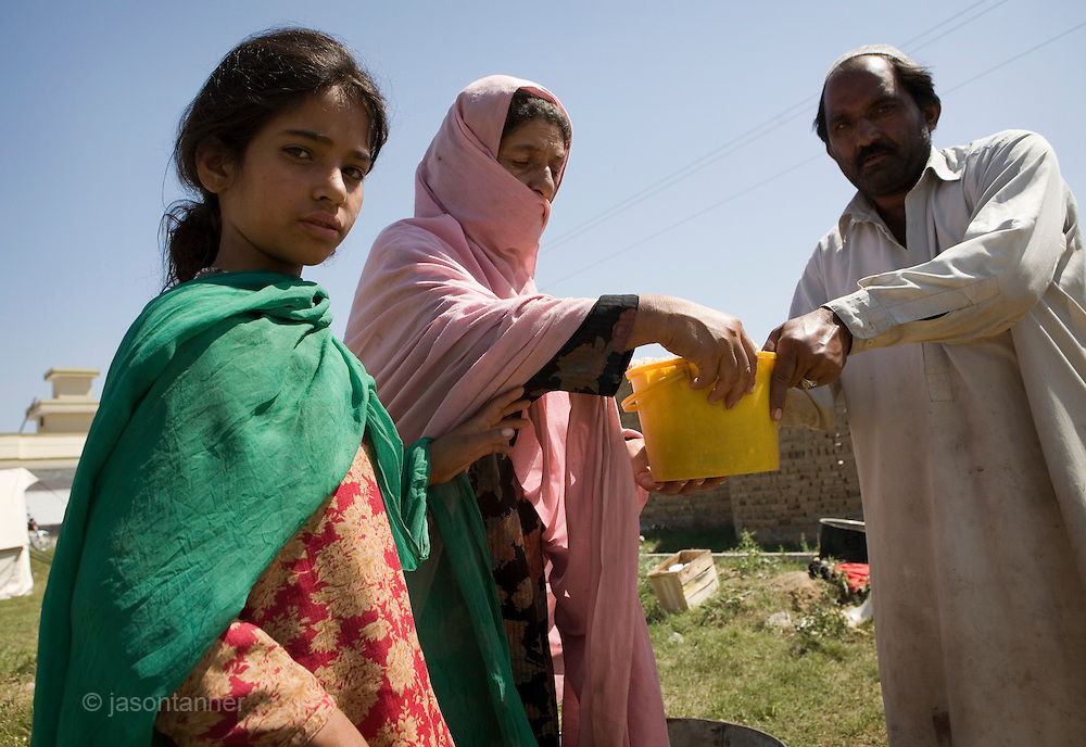 A young girl and her mum collect food and water courtesy of donations by the local political ANP party...Residents from SWAT valley begin arriving at Shaik Yaseen IDP camp at outside of Mardan in North West Frontier Province, Pakistan...More than 1400 families have reportedly registered as IDP's seeking shelter and food at the hastily arranged camp. According to UNHCR Some 500,000 residents have fled SWAT and neighboring provinces since August 2008. Last Thursday the Pakistan Government announced a military operation to 'eliminate' Taliban militants form the SWAT Valley. A further 1 million IDp are expected in the coming weeks as the military advances throughout SWAT valley towards achieving their military goals...