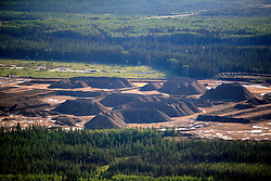 CANADA ALBERTA FORT MCMURRAY 23JUL09 - Aerial view of topsoil accumulated at clearcuts in the Boreal forest at the site of a tarsands mining operation north of Fort McMurray, northern Alberta, Canada...The tar sand deposits lie under 141,000 square kilometres of sparsely populated boreal forest and muskeg and contain about 1.7 trillion barrels of bitumen in-place, comparable in magnitude to the world's total proven reserves of conventional petroleum. Current projections state that production will  grow from 1.2 million barrels per day (190,000 m³/d) in 2008 to 3.3 million barrels per day (520,000 m³/d) in 2020 which would place Canada among the four or five largest oil-producing countries in the world...The industry has brought wealth and an economic boom to the region but also created an environmental disaster downstream from the Athabasca river, polluting the lakes where water and fish are contaminated. The native Indian tribes of the Mikisew, Cree, Dene and other smaller First Nations are seeing their natural habitat destroyed and are largely powerless to stop or slow down the rapid expansion of the oil sands development, Canada's number one economic driver...jre/Photo by Jiri Rezac / GREENPEACE..© Jiri Rezac 2009