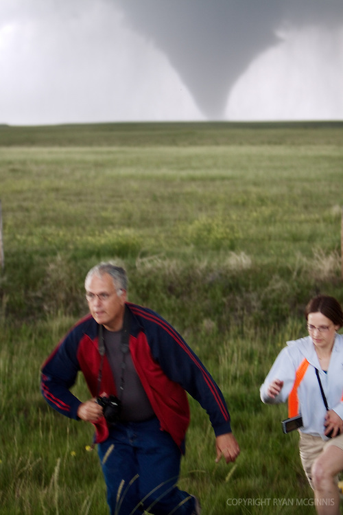 Storm chasers Tim Marshall and Lindsay Bennett run after deploying a probe in front of a rapidly advancing tornado in Goshen County, Wyoming, USA, June 5, 2009. Both are participating in Project Vortex 2. Project Vortex 2 is a two year National Science Foundation and NOAA funded science mission to study tornadoes and supercell thunderstorms.