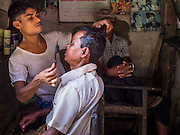 10 NOVEMBER 2014 - SITTWE, MYANMAR: A barber colors a customer's hair in his shop in the market in Sittwe, Myanmar. Sittwe is a small town in the Myanmar state of Rakhine, on the Bay of Bengal.    PHOTO BY JACK KURTZ