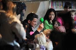 © Licensed to London News Pictures. 06/12/2011, London, PETER ANDRE holds a green rattle during songs with children.  BORIS JOHNSON and PETER ANDRE launch  the Love Libraries scheme at Shepherds Bush Library, London, Today 6th December. Love Libraries is a new scheme to encourage Londoners to read and participate in activities at their local libraries. Photo credit : Stephen Simpson/LNP