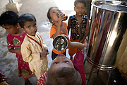Children are drinking purified water at a school run by Sonrisas de Bombay, a fast-growing Spanish NGO in Mumbai, India.