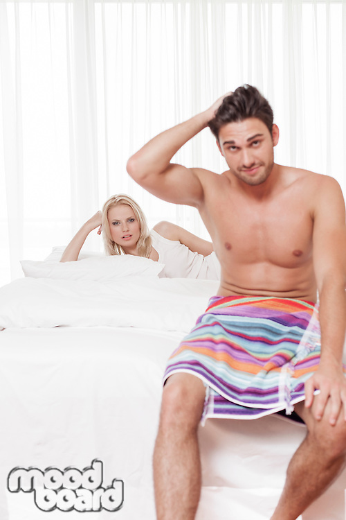 Portrait of shirtless young man with woman in background at hotel room